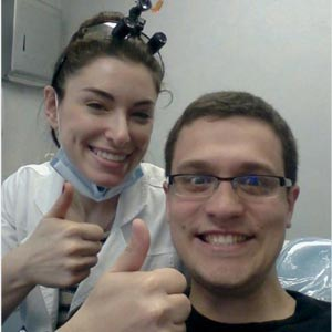 a female dentist and a male patient smiling