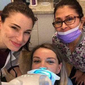 woman dentist and patient smiling with dentist assistant